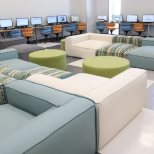 Communal area with large couches in the center and several computers lined along the walls.