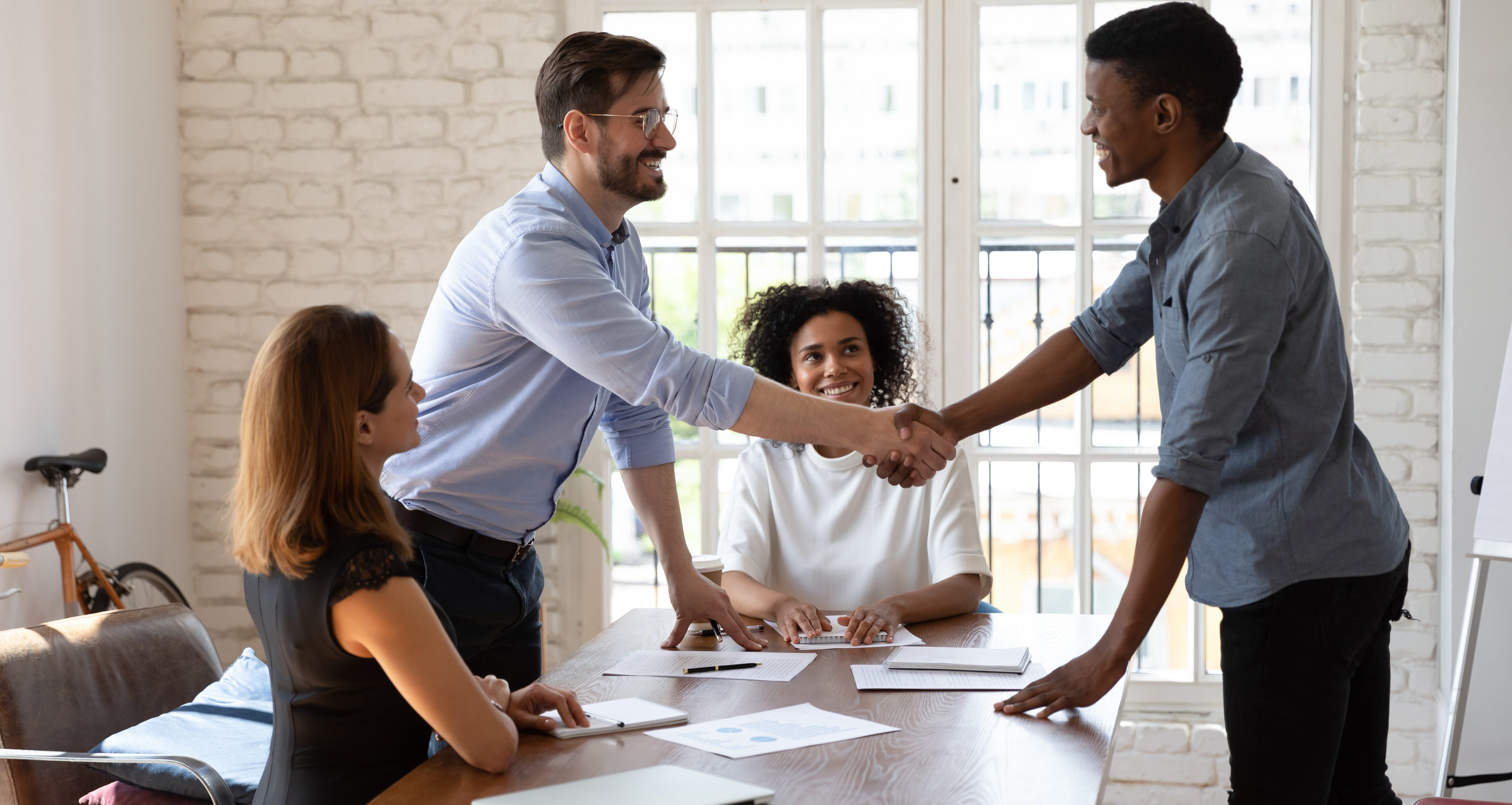 Smiling multiethnic male employees shake hands greet get acquainted at office meeting, happy diverse multiracial coworkers colleagues handshake congratulate with promotion close deal at briefing